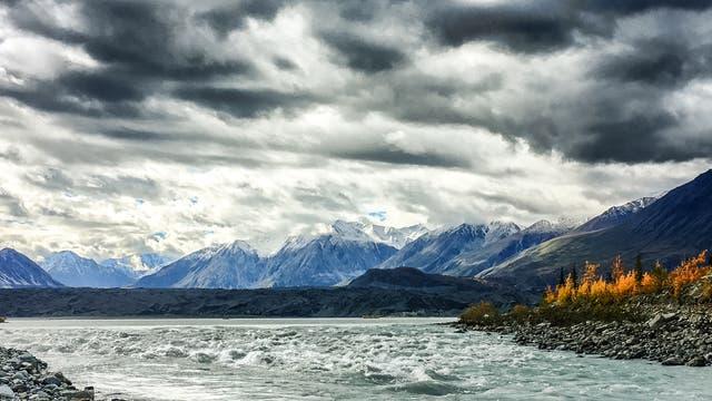 Ein breiter Schmelzwasserfluss zwischen Ufern mit Tundrenbewuchs. Im Hintergrund hohe Berge, darüber dramatische Wolken. Vermutlich haben die Autoren das Bild von der örtlichen Tourismuszentrale.