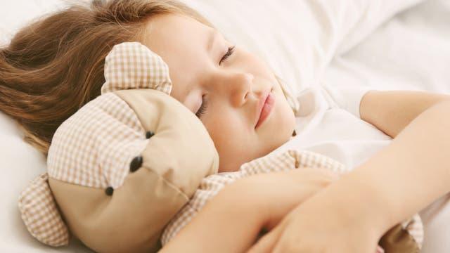Schlafendes Mädchen im Bett mit Teddybär