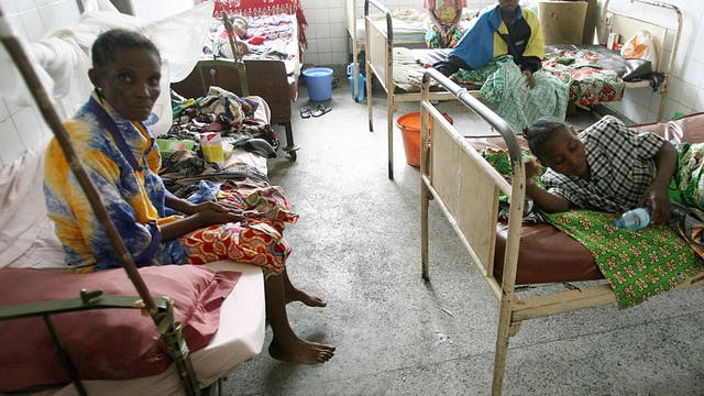 Foto eines Krankenzimmers mit altertümlichen Hospitalbetten, in denen Patientinnen mit ihren Habseligkeiten sitzen und liegen.