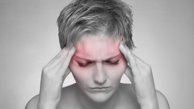 Frau mit Kopfschmerzen legt die Hände an die Schläfen
