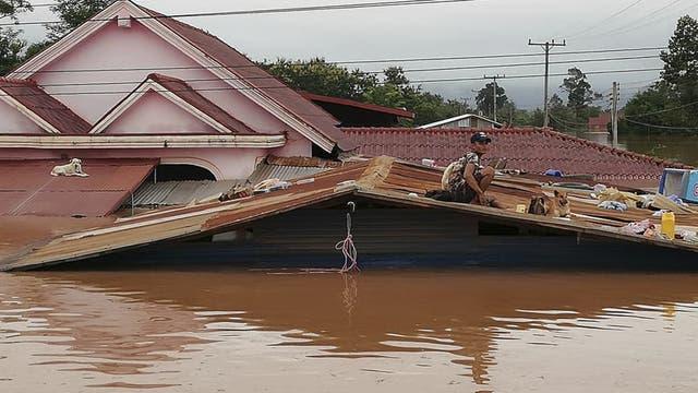 Ein Mensch sitzt auf dem Dach eines Hauses, das bis über die Fenster in schlammigem Wasser steht.
