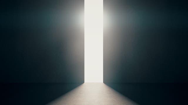 Gleißender Lichtschein dringt durch sich öffnenden Türspalt in dunklen Raum