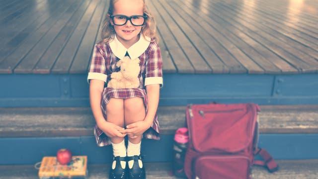 Ein junges Mädchen mit großer Brille sitzt mit angezogenen Beinen auf einer Treppe. Neben ihr steht eine rote Schultasche.