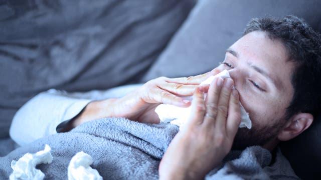 Ein Mann im Bademantel liegt im Bett und schneuzt sich in ein Taschentuch.