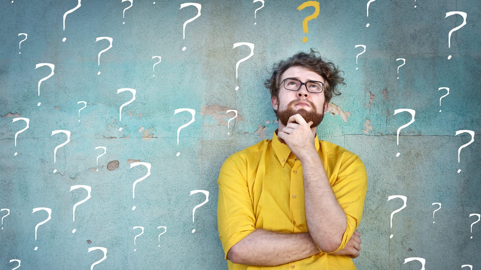 Mann vor einer mit Fragezeichen bemalten Wand.
