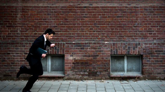 Ein Mann rennt auf seine Uhr schauend die Straße entlang.