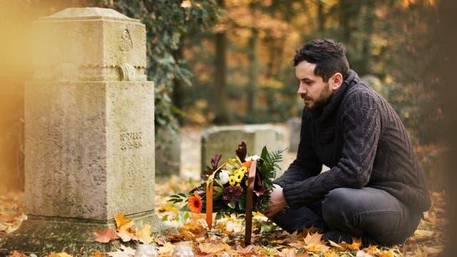 Ein Mann hockt vor einem Grab