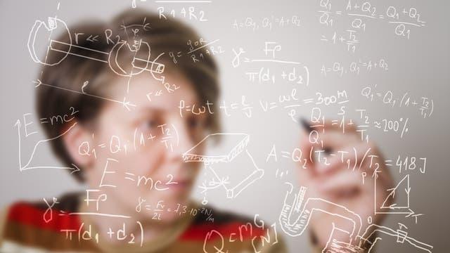 Eine Person scheint komplexe Mathematische Gleichungen und Zeichnungen an eine unsichtbare Tafel zu schreiben.