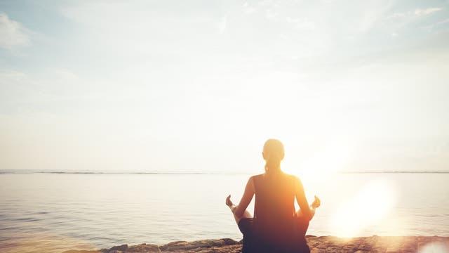 Frau meditiert bei Sonnenuntergang am Strand.