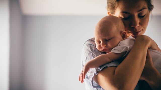 Eine Mutter hält ihr schlafendes Baby in den Armen.