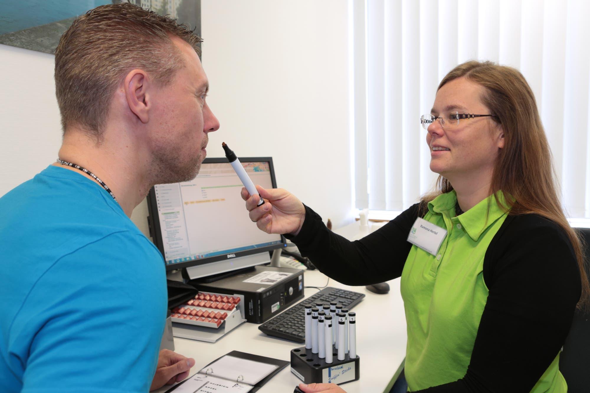 Eine Versuchsleiterin hält einem Teilnehmer einen Riechstick unter die Nase.