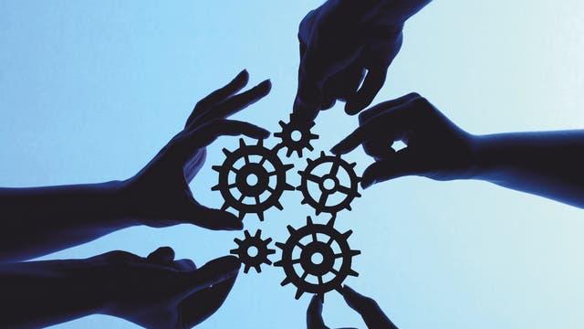 Reibungslose Zusammenarbeit: Viele Hände drehen an Zahnrädern
