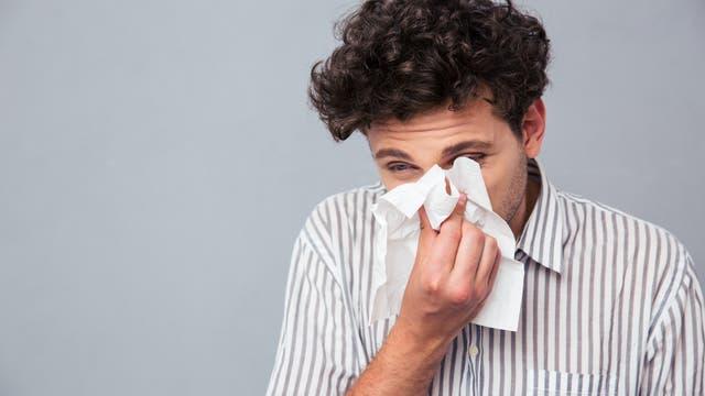 Mann niest ins Taschentuch