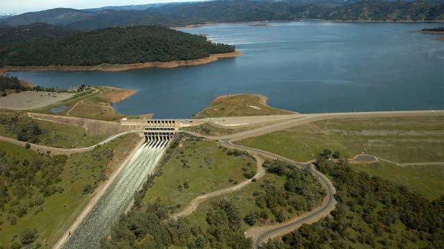 Der 1968 fertig gestellte Oroville-Staudamm ist mit 230 Metern der höchste der USA. Rechts der Damm selbst, links der in Beton gefasste Hauptauslass, dessen unterer Teil durch Erosion beschädigt wurde. Am linken Bildrand sieht man den Notüberlauf.