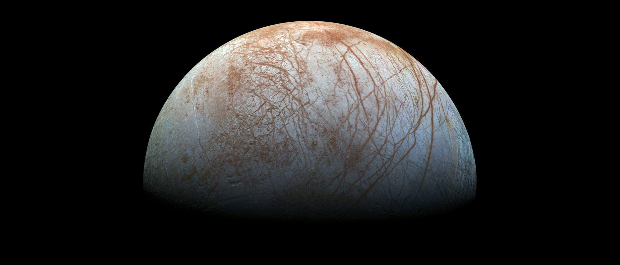 Der Jupitermond Europa hat eine Oberfläche aus Eis, über das gezackte, rotbraune Risse laufen.