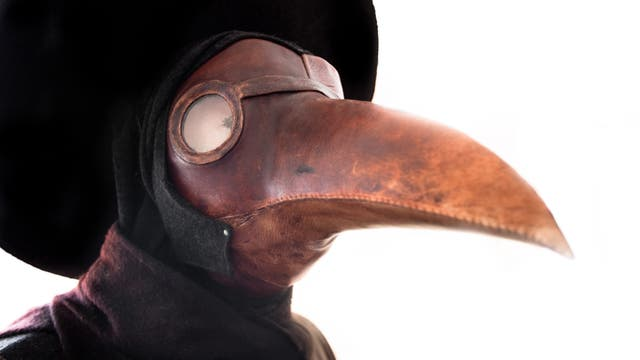 Ein Mensch trägt die damals bei Ärzten übliche Pestmaske