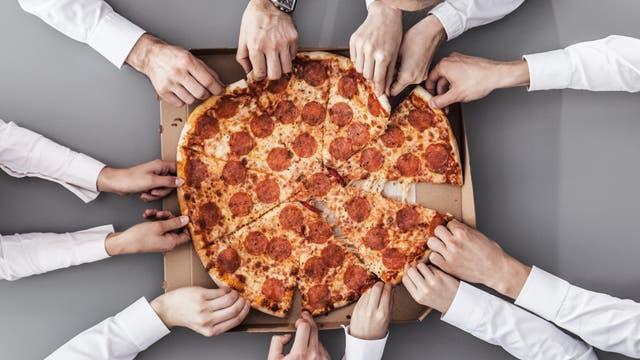 Arbeitskollegen essen gemeinsam Pizza