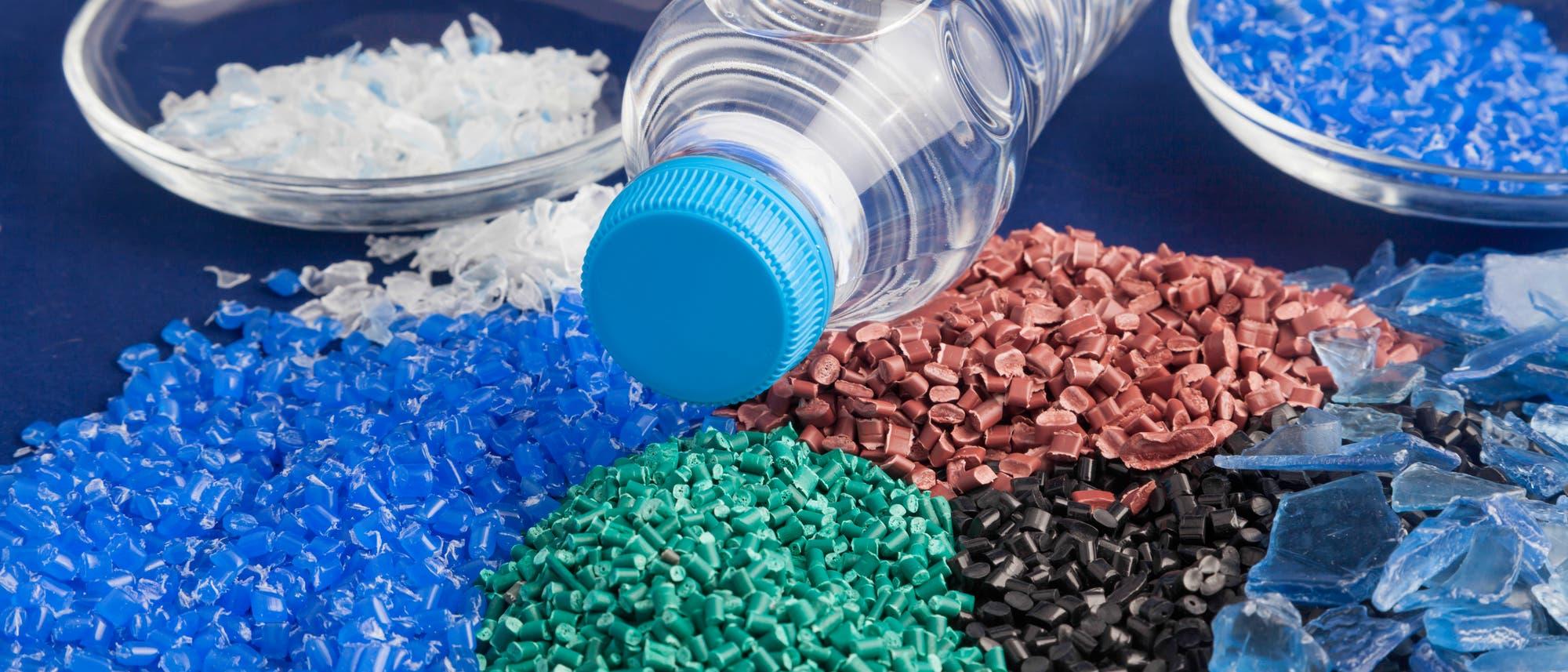 Plastikgranulat in verschiedenen Farben, in der Mitte eine PET-Flasche