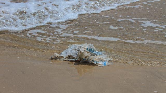 Eine Plastiktüte verschmutzt den Strand und belastet das Meer