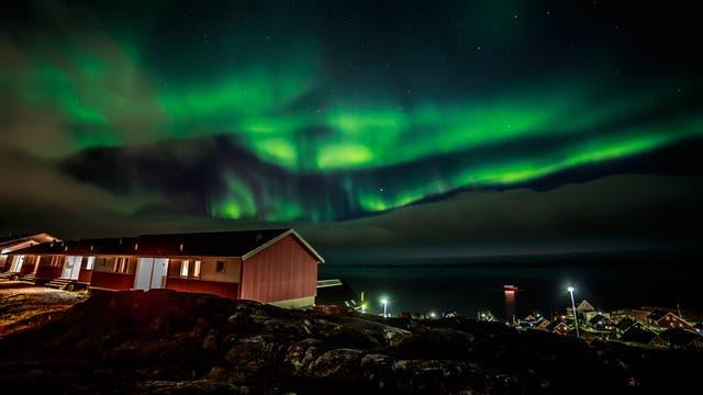 Polarlichter verzaubern die Nacht über einer grönländischen Siedlung