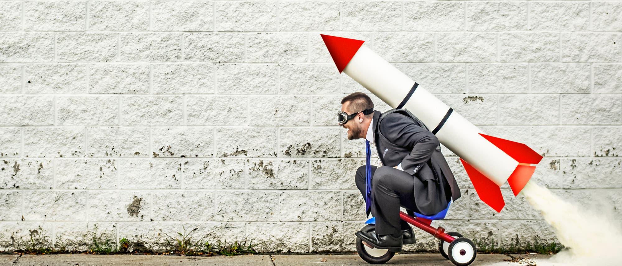 Ein Mann auf einem Dreirad startet mit Hilfe einer großen Rakete auf dem Rücken.