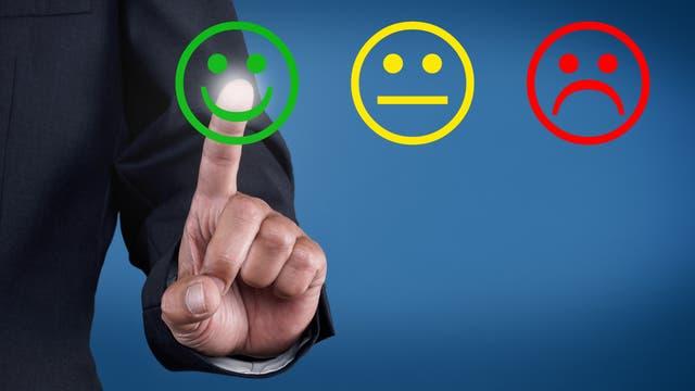 Finger der eine positive Bewertung abgibt, indem er auf den grünen lachenden Smiley tippt