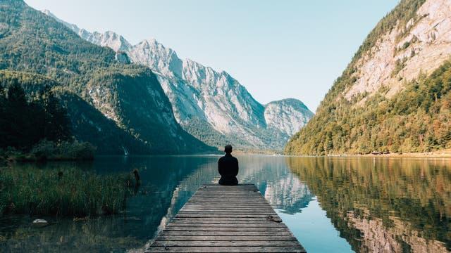 Mann sitzt auf Bootssteg und schaut auf den Königssee