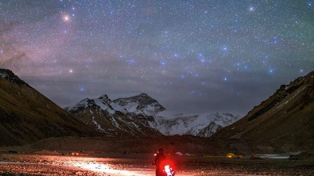 Der rötliche Antares im Sternbild Skorpion und die bläulichen Sterne des Centaurus leuchten über den hohen Berggipfeln des Himalaya. Der Motorrad-Tourist erreicht gerade das nördliche Basislager des Mount Everest in Tibet, das auf einer Höhe von 5170 Metern liegt.