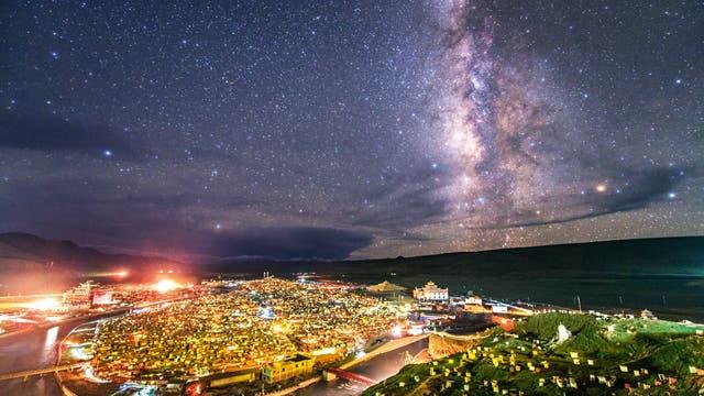 Das Band der Milchstraße leuchtet über der Siedlung Yarchen Gar im Hochland von Tibet. Hier, in 4000 Meter Höhe, leben und beten mehr als 10000 buddhistische Mönche und Nonnen unter einfachen Verhältnissen in ihren kleinen Meditationshütten.