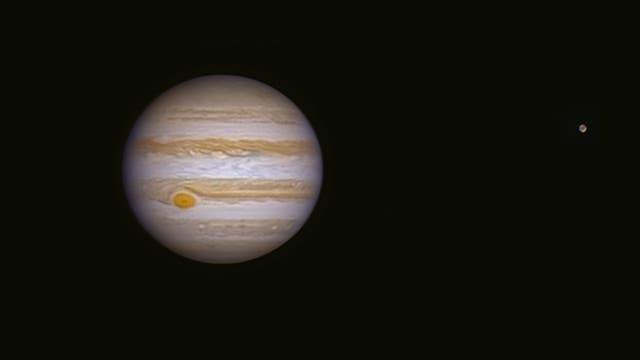 Jupiter und sein Mond Ganymed in der Schwärze des Weltalls.