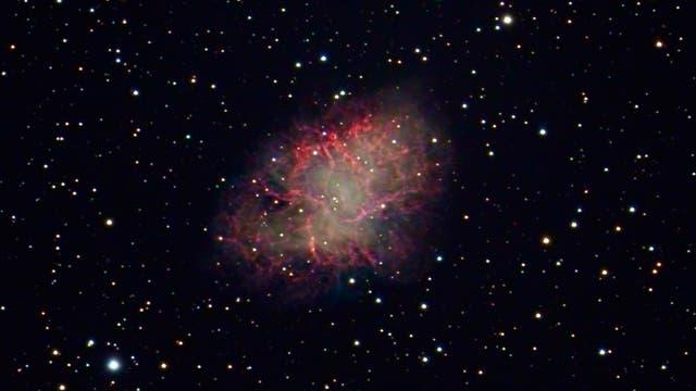 Der rund 16 mag helle Pulsar inmitten des Krebsnebels ist astrofotografisch leicht zugänglich. Auf lang belichteten Aufnahmen wie dieser treten die feinen roten Filamente des Nebels hervor, die dem Objekt seinen Namen gaben.