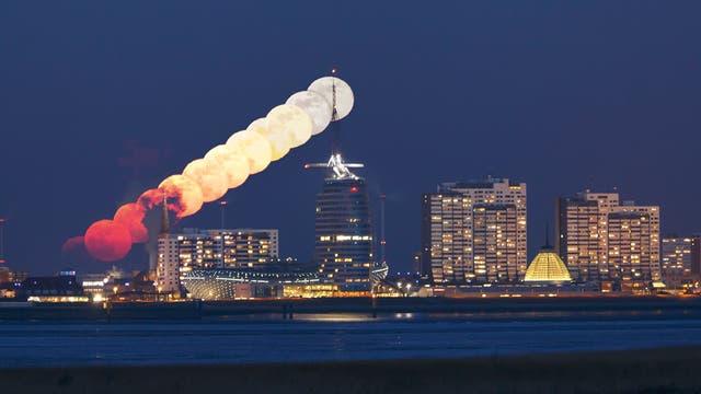 """Am 2. März 2018 gewann Maciej Libert dieses Komposit vom Mondaufgang über Bremerhaven. Er schreibt: """"Durch viele Staubpartikel in den unteren Atmosphärenschichten erschien der Mond ungewöhnlich tiefrot– ein wunderschöner Anblick!"""""""