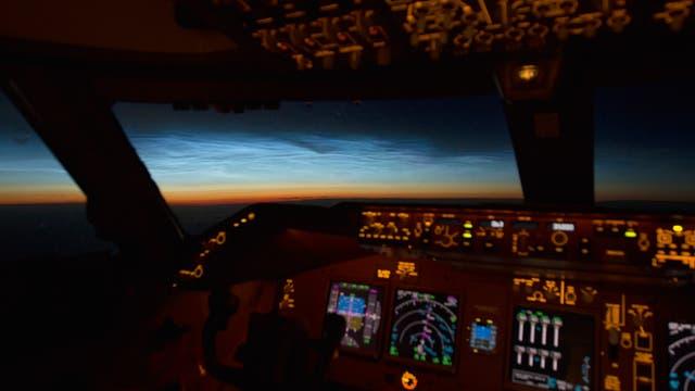 Leuchtende Nachtwolken aus dem Cockpit