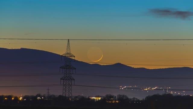 Zunehmender Mond als Sichel über Bergen.