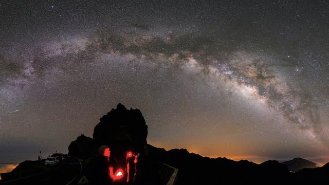 Über einem rot beleuchteten Berg ist die Milchstraße gut zu erkennen.