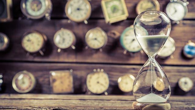 Sand einer Sanduhr verrinnt vor vielen Uhren
