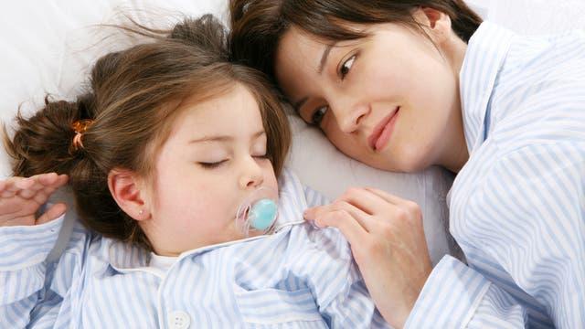 Kleinkind schläft neben seiner Mutter