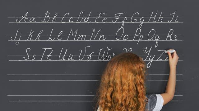Mädchen schreibt das Alphabet an die Tafel
