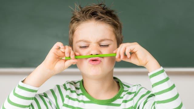 Schuljunge spielt mit Stift