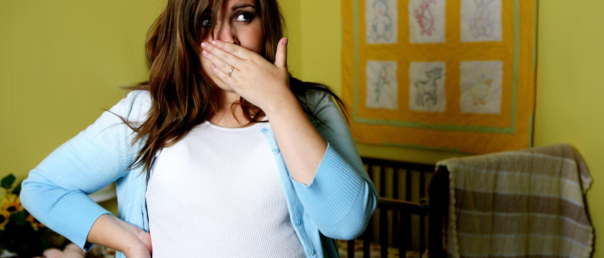 Eine schwangere Frau hält sich die Hand vor den Mund. Sie leidet offenbar unter Übelkeit.