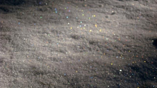 Die bunten Lichtblitze frischer Kristalle lassen sich nur mit fotografischen Tricks festhalten, etwa einer kurzen Belichtungszeit und Defokussierung. Damit erscheint der Schnee zugleich dunkel und unscharf.