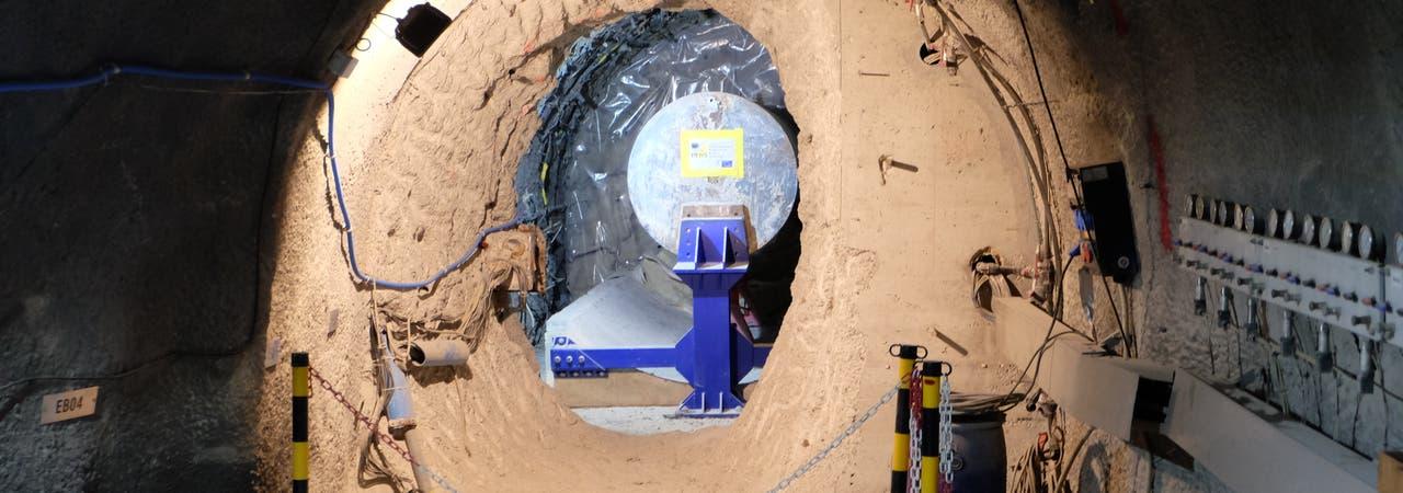 Ein Stahlzylinder von der Größe eines Atommüllfasses ist in einen unterirdischen Stollen eingebaut.