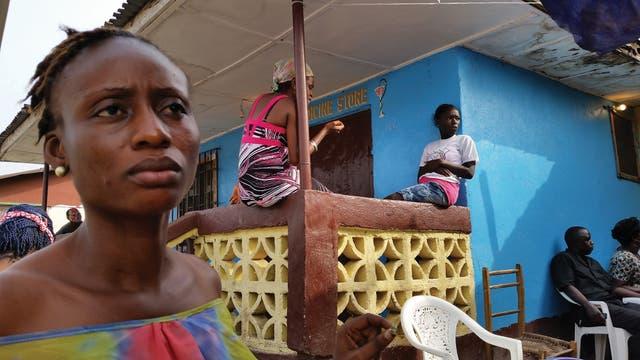 Afrikaner sitzen und stehen vor einer Apotheke.