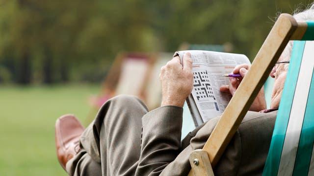 Älterer Mann löst Kreuzworträtsel im Gartenstuhl