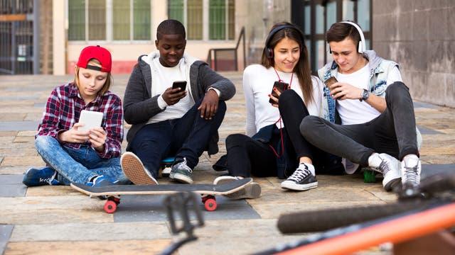 Glückliche Teenager verbringen ihre Zeit, um gemeinsam auf das Smartphone zu schauen