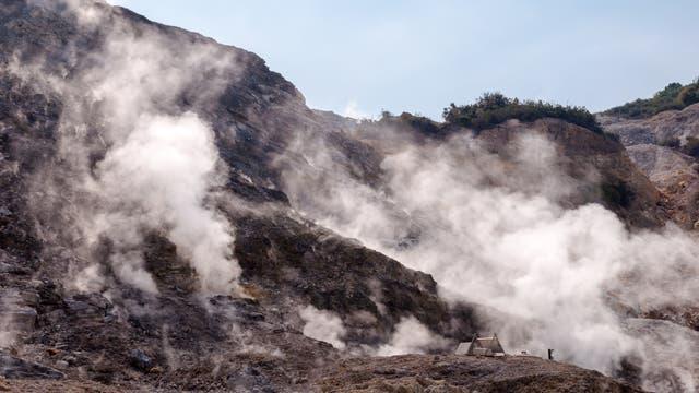 Dampfschwaden steigen von einem Hang aus dunklem vulkanischen Gestein auf