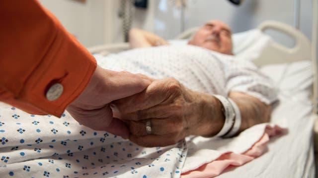 Frau hält sterbendem Mann die Hand