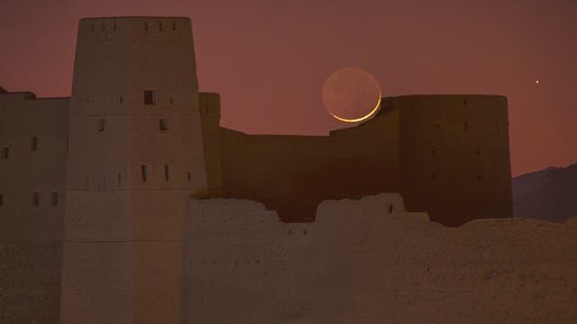 Mond und Saturn über der Festung von Bahla in Oman