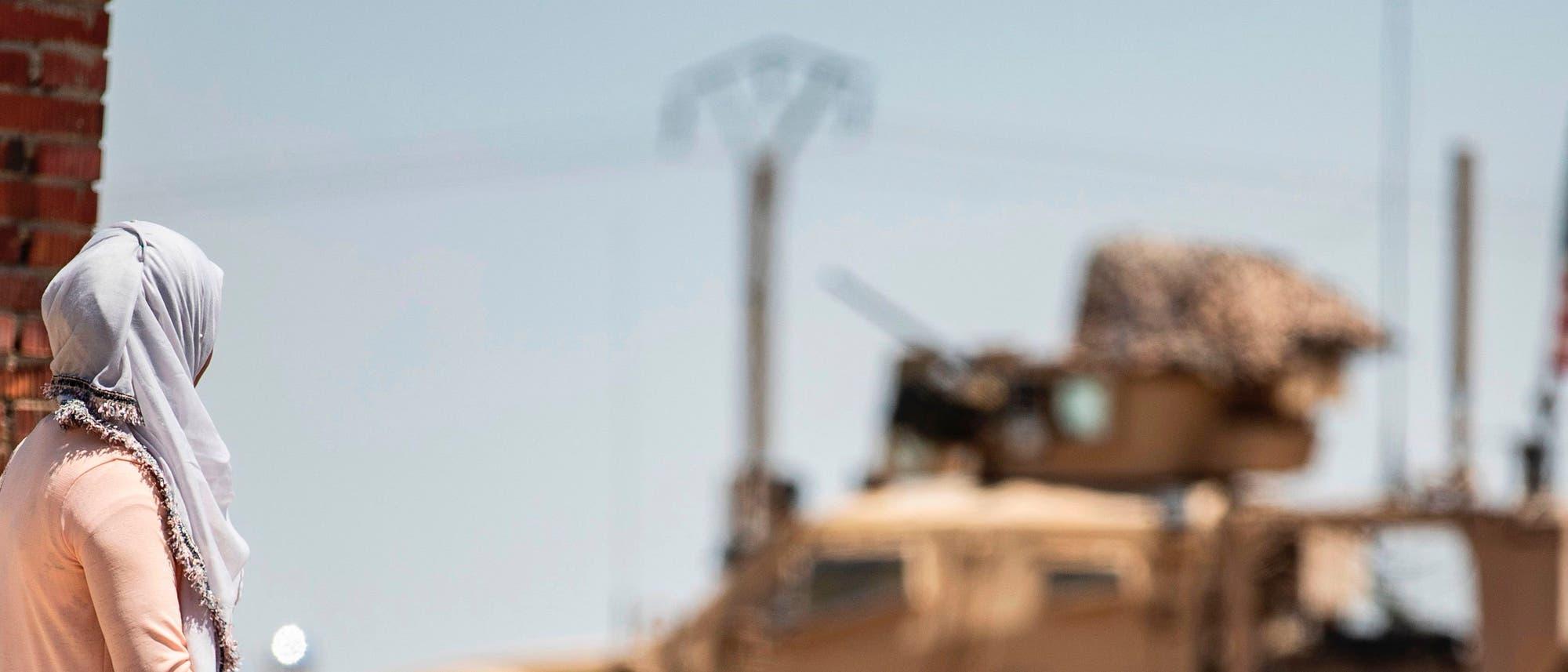 Menschen in Syrien beobachten ein US-Militärfahrzeug.