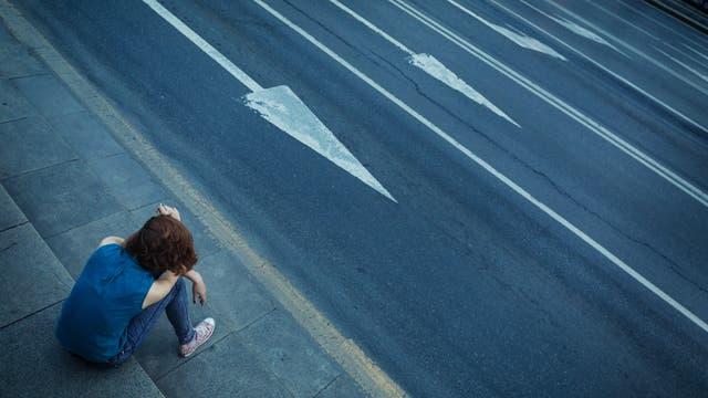 Ein Teenager an einer vierspurigen Straße